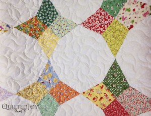 Angela quilted this 1930s kite block quilt with an edge to edge design called Bell Blossom