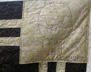 Marie's Punisher quilt with free motion skulls in the cornerstones - QuiltedJoy.com