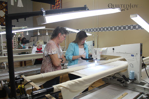 Angela works with a students in one of the Longarm Schoolhouse classes