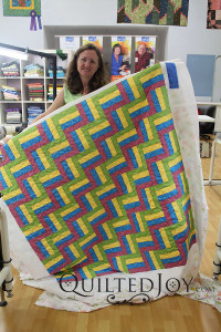 Cheryl shows off her rail fence quilt after her rental certification class - QuiltedJoy.com