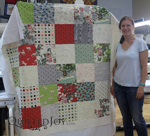 Erin pieced this layer cake in the hours between dropping her kids off at school and coming to Quilted Joy for her longarm machine rental.