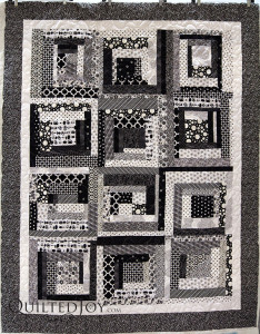Karee made a black and white log cabin for her teenaged grand daughter. Quilter Angela Huffman added a fun all over Daisy pantograph. - QuiltedJoy.com