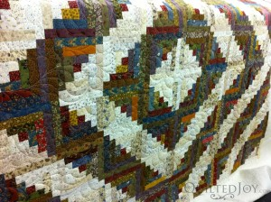 Deborah's scrappy log cabin with all over quilting by Angela Huffman