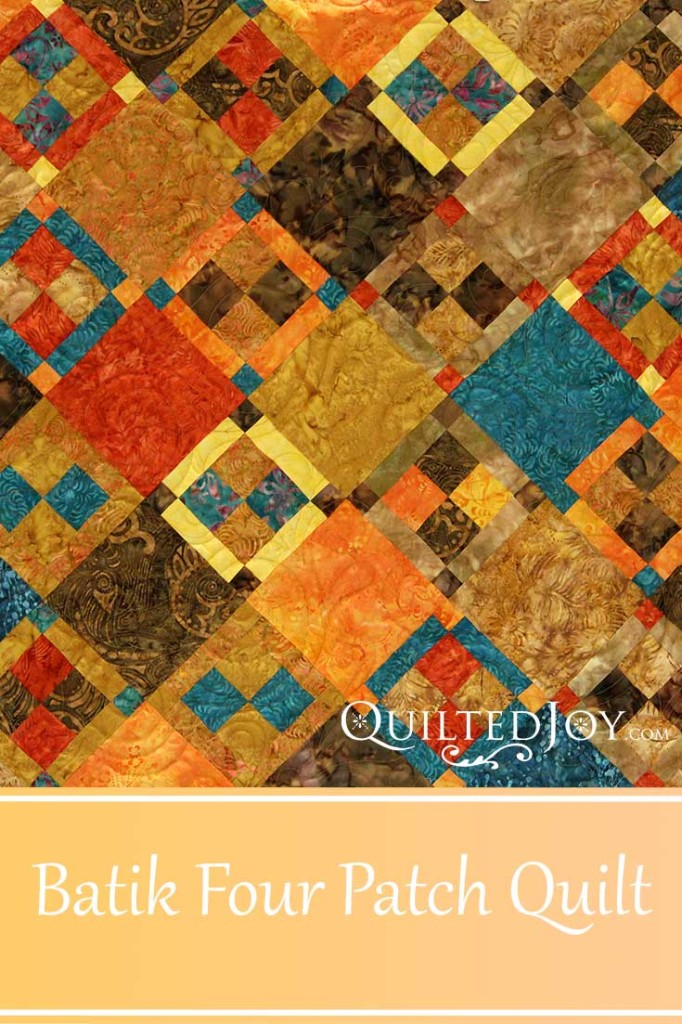 This batik wall hanging has an alternating four patch block on point. Longarm quilter Angela Huffman added the Brittany pantograph for an all over quilting design