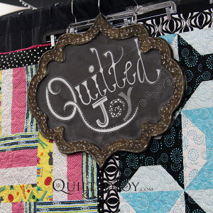 Quilted Joy sign hanging in the trade show booth
