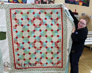 Snowball blocks alternating with four patch quilt. Maggi quilted this with the Lime Tree pantograph on an APQS longarm machine at Quilted Joy.