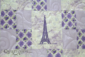 The Eiffel Tower is embroidered into the center block. The Purple Parisian is an alternating four patch quilt with a fun Parisian theme. Quilting by Angela Huffman