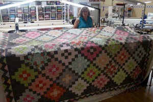 Debbie's massive Trip Around the World quilt. Quilted with a feather meander design board.