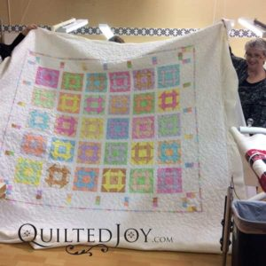 LuAnn's bright and colorful Churn Dash block quilt. Quilted at QuiltedJoy.com