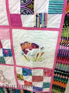 Embroidered fish on a baby quilt. Quilted at QuiltedJoy.com