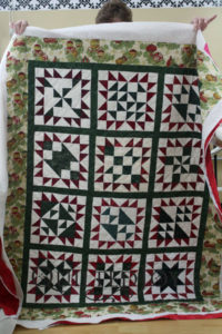 Pat's block of the month wasn't originally going to be a Christmas quilt, but she embraced the theme. Pat came to Quilted Joy to quilt this on our APQS longarm machines and used an orange peel design board.