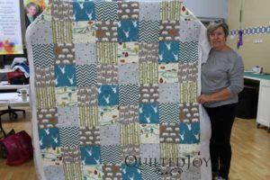Connie shows off her new grandson's first quilt after quilting it at Quilted Joy