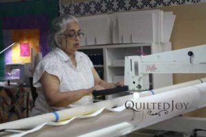A member of Louisville Nimble Thimbles uses the APQS Millie to quilt a charity quilt