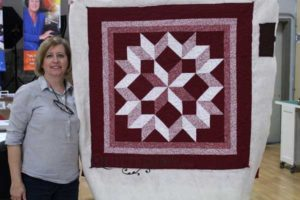 Polly with her broken star quilt after her rental certification class at Quilted Joy