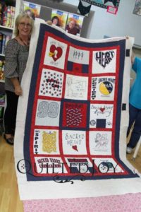 Pam shows off the T-shirt quilt she made at Quilted Joy during the T-shirt Quilt Camp