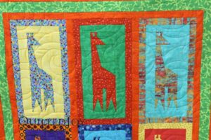 Detail of the paper pieced giraffes on an adorable baby quilt. Quilting pattern is Turbulance by Apricot Moon