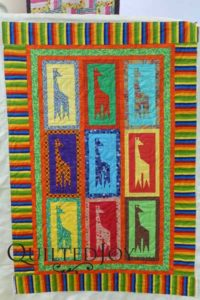 Adorable giraffe quilt with foundation piecing. Quilted on APQS longarm machine at Quilted Joy