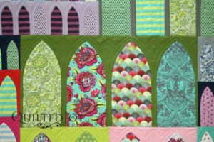 """""""Gothic Arches"""" is a Tula Pink design. Angela chose to use custom quilting techniques to enhance the patterns of the fabrics used in the top."""