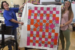 Karen and her granddaughter show off their first completed quilt on the longarm machine!