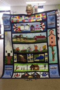 Karen shows off her winning quilt from Row by Row 2016