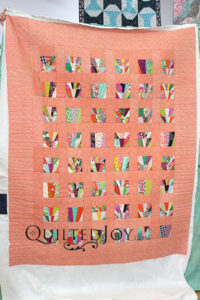 Erin's impromptu piecing quilt with straight line ruler quilting at Quilted Joy