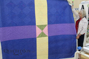 Donna's strip sets quilt with a pieced back was quilted on a longarm machine at Quilted Joy