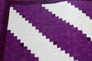 A beautiful purple and white log cabin quilt. Quilted by Angela Huffman