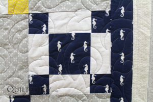 This quilt for a lucky baby boy and his parents sports tiny seahorses and lots of leaves.