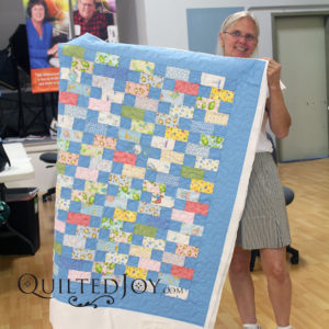 Kym shows off her quilt after her rental certification class at Quilted Joy