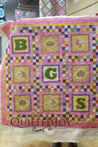 Pink baby quilt with letter blocks