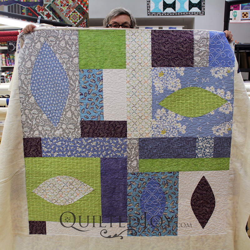 Terry quilted her modern quilt with a freehand meander on a APQS longarm machine at Quilted Joy