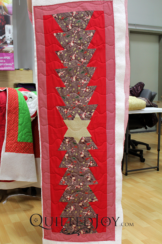 Valerie's Christmas Tree Table Topper looks amazing after she quilted it at Quilted Joy!