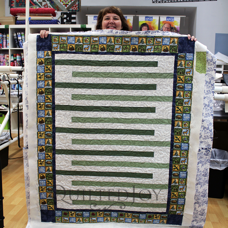 Christine made this beautiful sage green and ivory quilt for her nephew. Using the Toss Up Pantograph, she learned to use our long arm machines on this Woodland Winter Quilt.