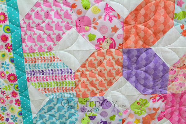 Debbie's baby quilt is so bright and cheerful! She quilted this on a longarm quilting machine at Quilted Joy.