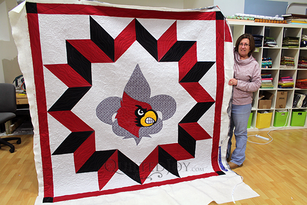 Judy's University of Louisville quilt featuring a Fleur De Lys and the UofL Cardinal. She custom quilted this beauty at Quilted Joy.