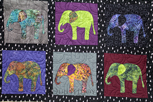 Appliqued elephants on a quilt