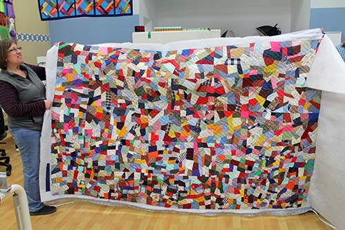 Vintage quilt made with scraps of clothing and other materials