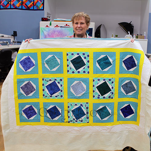 Bonnie displays her blue and yellow kid's quilt after quilting it on a longarm machine at Quilted Joy