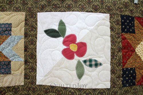 Applique flower on patchwork sampler quilt