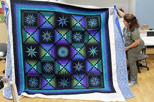 Anna Maria shows off her Moon Glow Quilt after her longarm machine rental at Quilted Joy