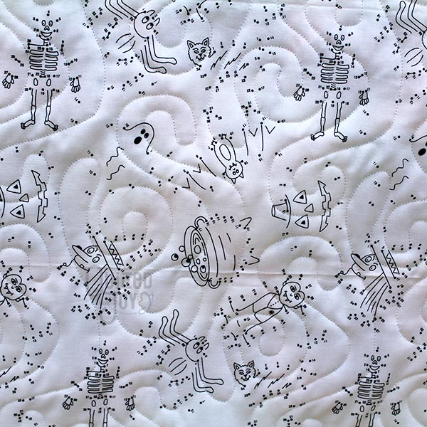 Colleen displays her Boo To You Quilt after renting a longarm machine at Quilted Joy
