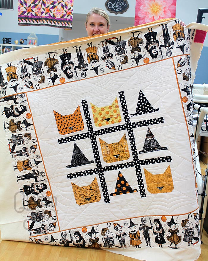 Melissa shows off the Tic Tac Cat Quilt after longarm quilting it at Quilted Joy