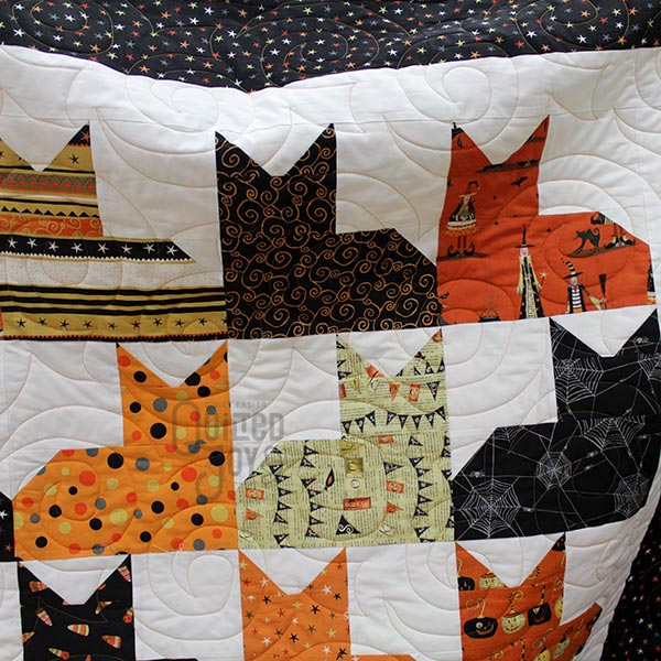 Rita admires her Halloween Pins and Paws quilt after longarm quilting it at Quilted Joy