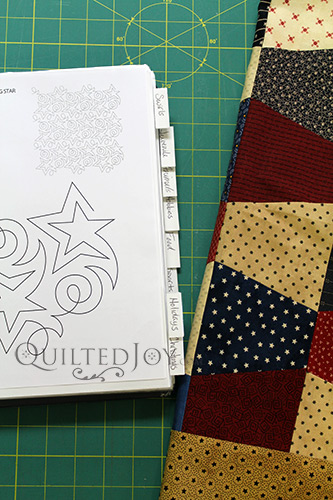 Tumbler Block quilt next to a binder filled with different quilting design possibilities.