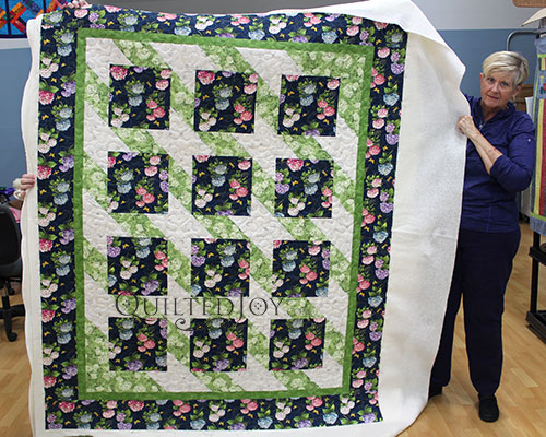 Beverly's Floral Focal Fabric Quilt after her longarm machine rental at Quilted Joy