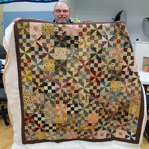 Dennis shows off his Pinwheel and 9 Patch Quilt after longarm quilting at Quilted Joy