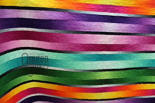 Carol shows off her ombre stripes quilt after renting a longarm machine at Quilted Joy
