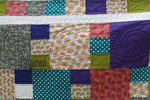 Chris shows off her quilt after renting a longarm machine at Quilted Joy
