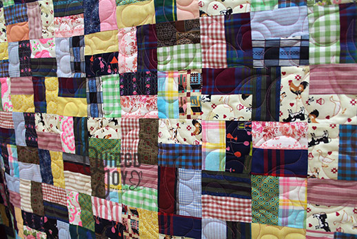 Dennis shows off his split rail quilt after renting a longarm machine at Quilted Joy
