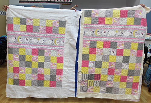 Jennifer shows off two baby quilts after longarm quilting them at Quilted Joy